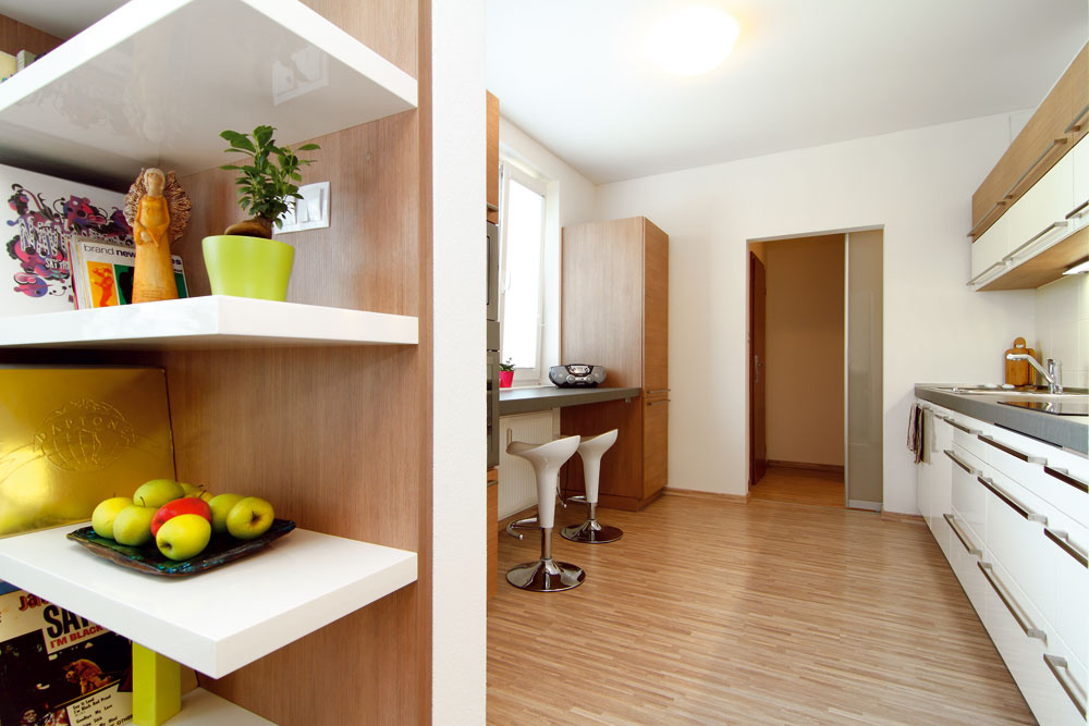 Vďaka posuvným dverám sa dá kuchyňa pekne prepojiť sobývačkou, ale aj uzavrieť – podľa situácie. Praktickej komore za kuchyňou, ktorá slúži ako odkladací priestor na všetko možné, zasa vďačia kuchyňa aj obývačka za to, že nemusia byť veľmi zaplnené nábytkom. Pôsobia tak vzdušnejšie avoľnejšie.