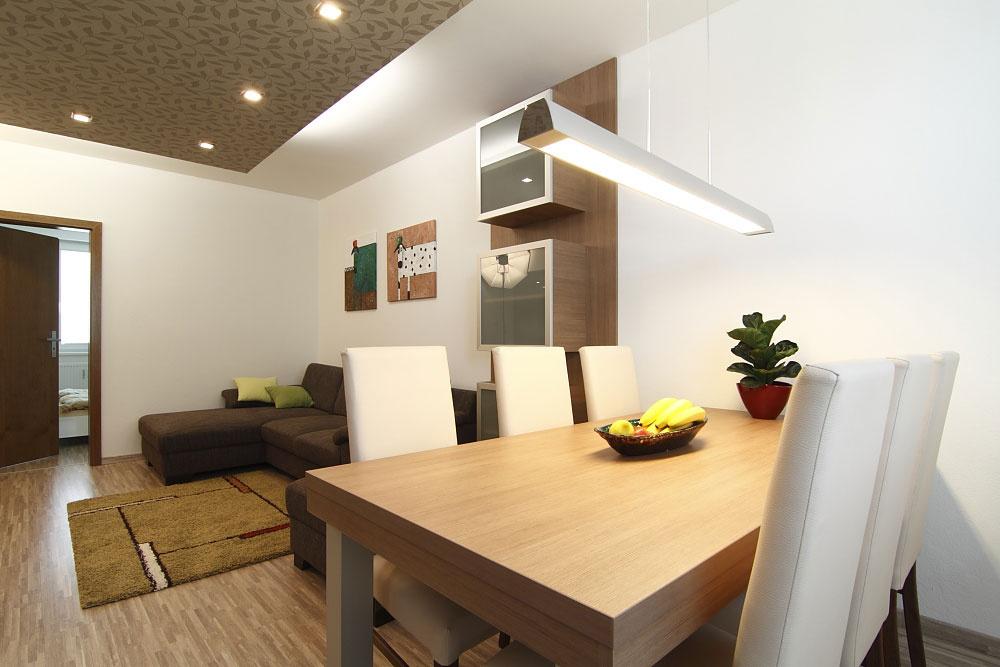 Nábytok v obývačke a jedálni poňal architekt minimalisticky a skôr kompozične. Vytiahnuť otapetovanú stenu až na strop sa nakoniec ukázalo ako dobrý ťah.