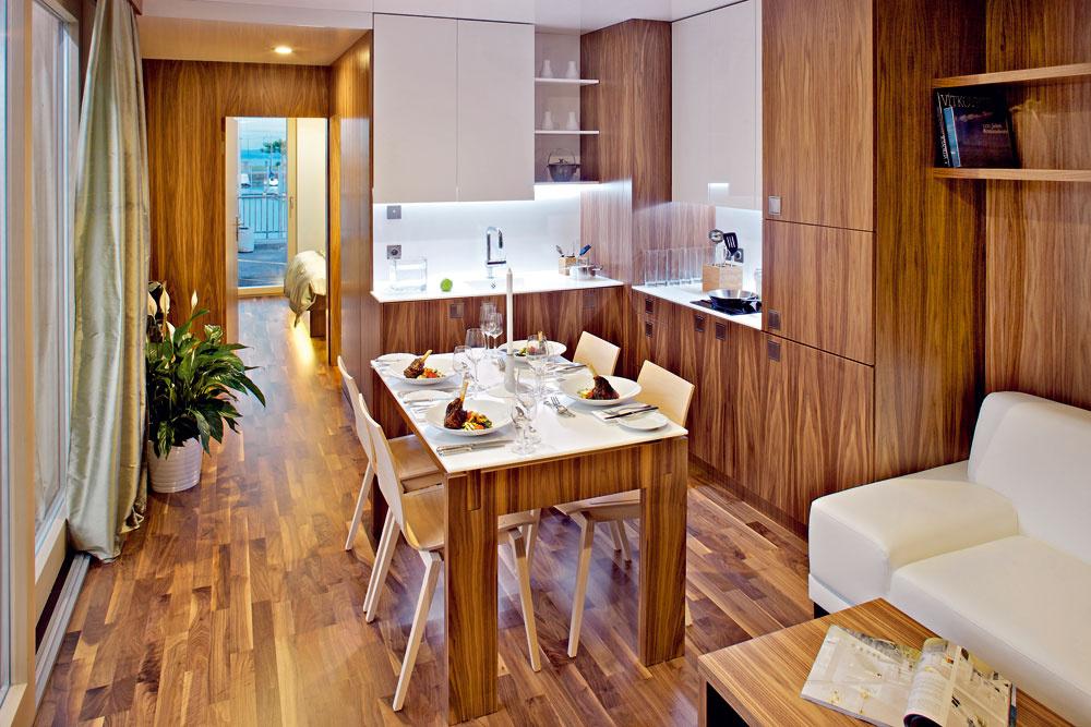 Kzákladnej výbave freedomčeka patria jednoduchý moderný nábytok aj kuchynské spotrebiče. Takto vyzerá hlavný obytný priestor väčšieho typu domčeka so samostatným vstupom, ktorý stojí vo Švajčiarsku pri Bodamskom jazere (pohľad cez kuchyňu apredsienku smerom kspálni).