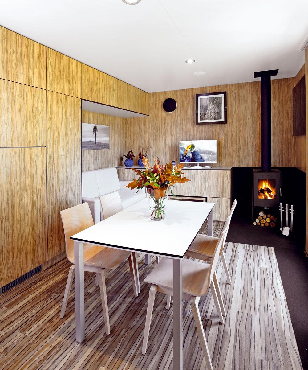 Pohľad opačným smerom – zkuchyne do obývačky. Štandardne je domček vybavený nástennými elektrickými vykurovacími telesami, variantom sú infrapanely. Autori však odporúčajú kozubové kachle, ktoré domček parádne vykúria obnoviteľným drevom.