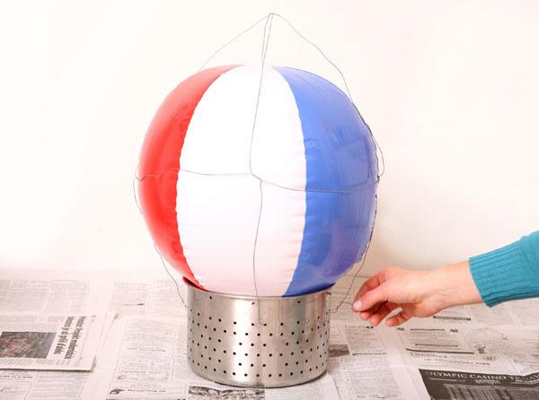 1 Zbalóna adrôtu si vyrobíte konštrukciu tienidla. Balón položte nafukovacím otvorom dole na cedidlo aobmotajte ho drôtmi tak, aby sa obidva konce zužovali.