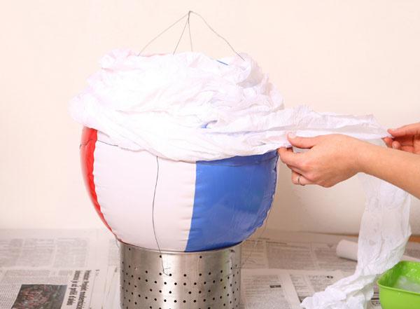 3 Krepový papier pretrhnite po šírke na polovicu. Postupne ho namáčajte do lepidla aobmotávajte ním balón. Vo vrchnej časti nechajte malý vetrací otvor.