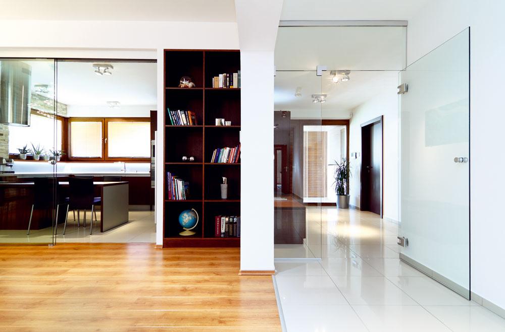 Pohľad zobývačky smerom kvstupným dverám. Veľké sklené plochy oddeľujú azároveň nedelia. Aj vďaka nim pôsobí denný priestor domu vzdušne apriestranne.
