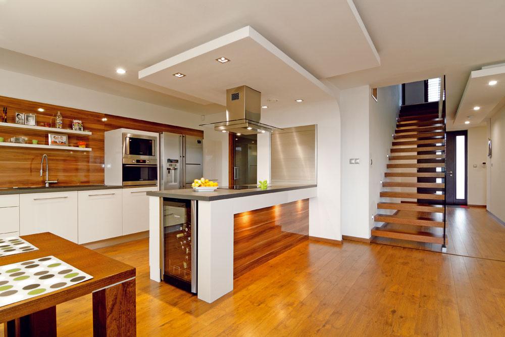 """Návrh interiéru vychádzal podľa slov architekta, rovnako ako pri exteriéri, zpožiadaviek investora. Dispozičné riešenie malo byť vzdušné, priestranné azároveň pohodlné. Vďaka drevostavbe nebol žiadny problém namontovať puzdrové dvere vedúce do komory vedľa kuchyne. Praktická roletová skrinka zboku kuchynského pultu rýchlo skryje všetok prevádzkový """"neporiadok""""."""