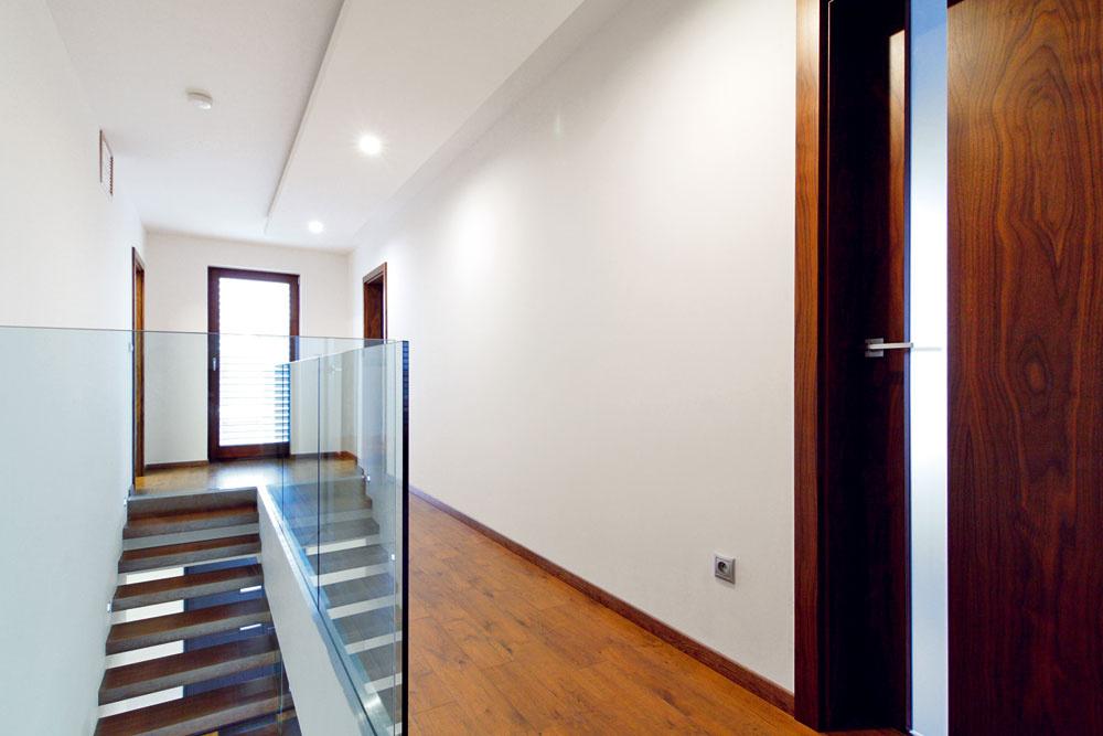 Aby schodisko nepôsobilo rušivo, vzdušnosť mu dodali sklenými prvkami. Priestoru dominujú neutrálne farby, ktoré domáca pani oživuje len pestrými doplnkami vizbách.