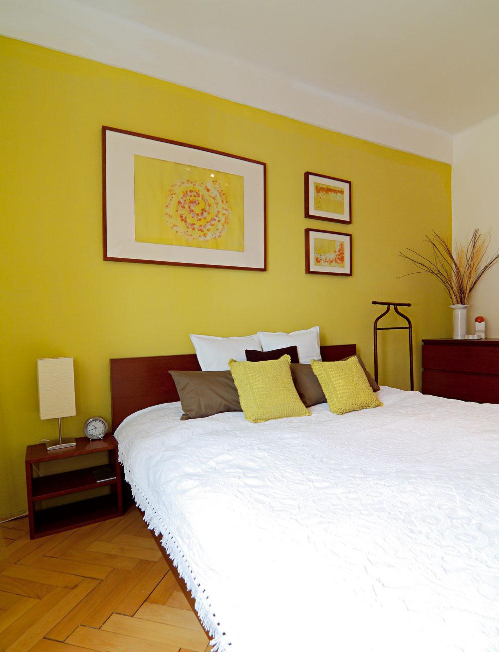 """""""Spaniareň"""" na mieru  Drevené parkety prešli kozmetickou úpravou anočný stolík bol vytvorený zo zvyškového dreva. Sfarebnou stenou vjednom rytme tancujú ručne vyrobené doplnky aobrázky – zfarby na stenu, ktorá zostala."""