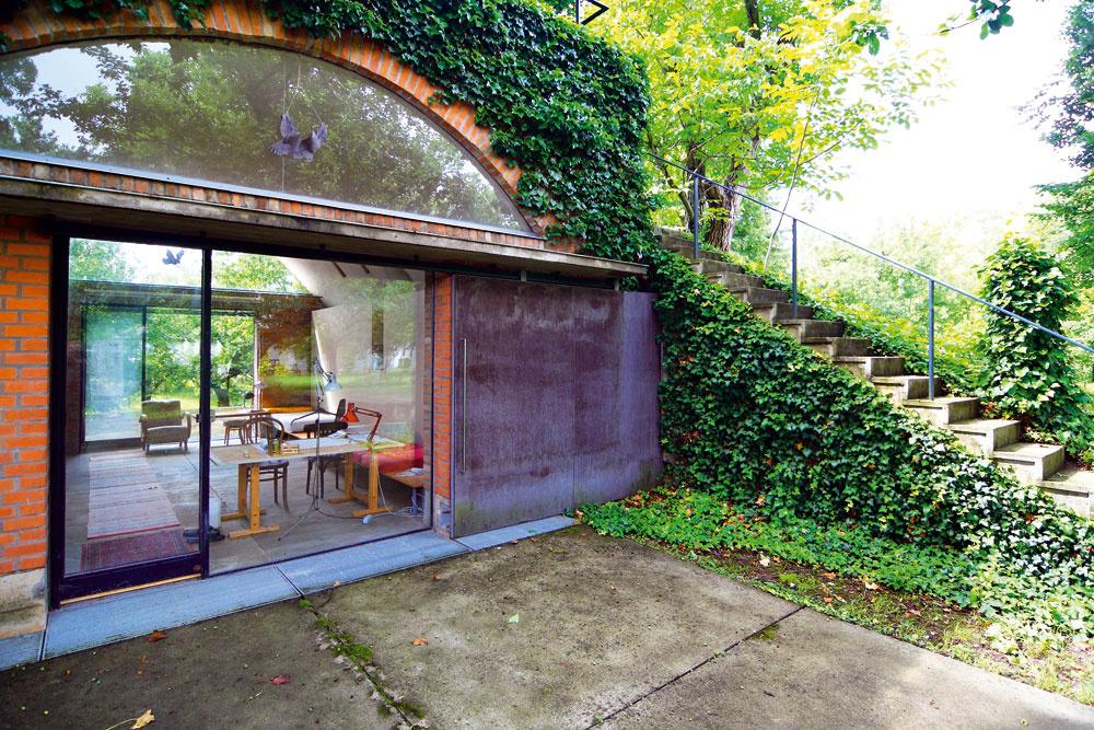 Na streche objektu je krytá terasa prístupná po betónovom schodisku. Schodiskové stupne, zasadené v záplave brečtanu, pôsobia vďaka lemovaniu betónovou obrubou subtílne a ľahko.