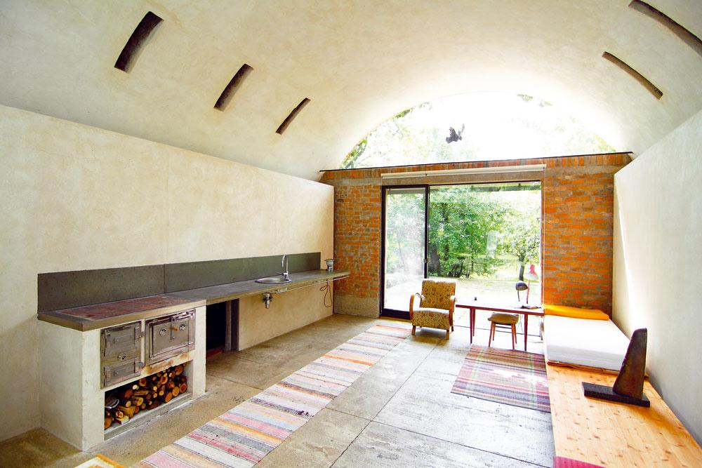 Za stienkou zmliečneho skla sa skrýva toaleta sumývadlom. Betónová podlaha je odspodu zateplená vrstvou polystyrénu alen nalakovaná. Výborne dopĺňa režné murivo aomietané steny bez maľby. Kuchynská linka sa netvári, že tu žije usilovná gazdinka. Sme predsa vdomácom ateliéri architekta ana uvarenie kávy to stačí. Tu sa nevarí, tu sa tvorí. Výsledkom takejto tvorivosti je aj pracovná doska. Dve cementotrieskové dosky vyplnené betónom analakované. Je to prosté, anapriek tomu funkčné. Alebo práve preto?