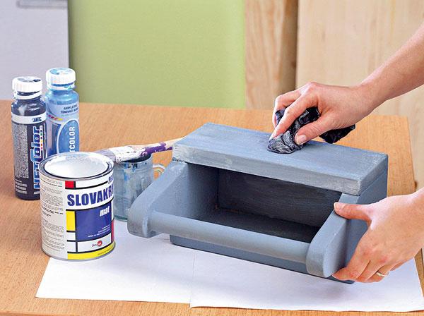 Debničku napenetrujte bielou farbou zriedenou svodou (vpomere 1 : 1). Potom ju natrite sivou farbou (zmiešate bielu farbu stónovacími). Na zaschnutú sivú farbu vtierajte vlhkou handričkou bielu farbu avytierajte dostratena.
