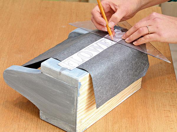 Cez kopírovací papier prekreslite na debničku text avymaľujte neriedenou bielou farbou.