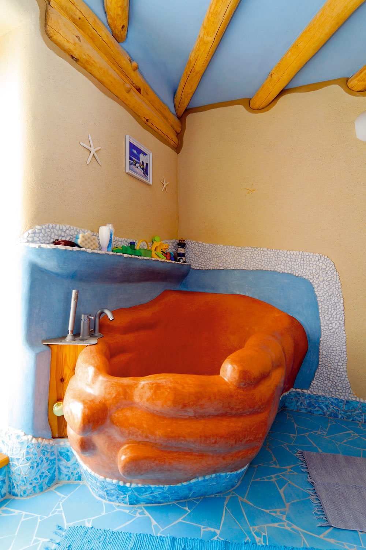 Základný tvar vane postavili zpóbetónových tvárnic, dovymodelovali ju do tvaru spojených dlaní apovrch dokončili marockou štukou – Tadelaktom. Aj tu sa prejavila osobná pečať majiteľov, tvar je totiž vernou kópiou rúk pani domácej. Na stenách je omietka skoralovým pieskom sdrobnými úlomkami mušlí. Vymyslel ju avo svojej firme aj ponúka pán Michal.