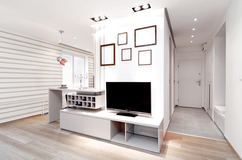 """Svetlé farby, jednotný štýl zariadenia aotvorená dispozícia dodali bytu vzdušnosť – obývačka je otvorená tak smerom do kuchyne, ako aj do chodby. """"Výbežok"""" medzi kuchyňou apredsieňou skrýva kúpeľňu aWC – vďaka rozmiestneniu nábytku ariešeniu stien aj podláh však pôsobí nenápadne, akoby sa len jemne zahryzol do inak kompaktného denného priestoru."""