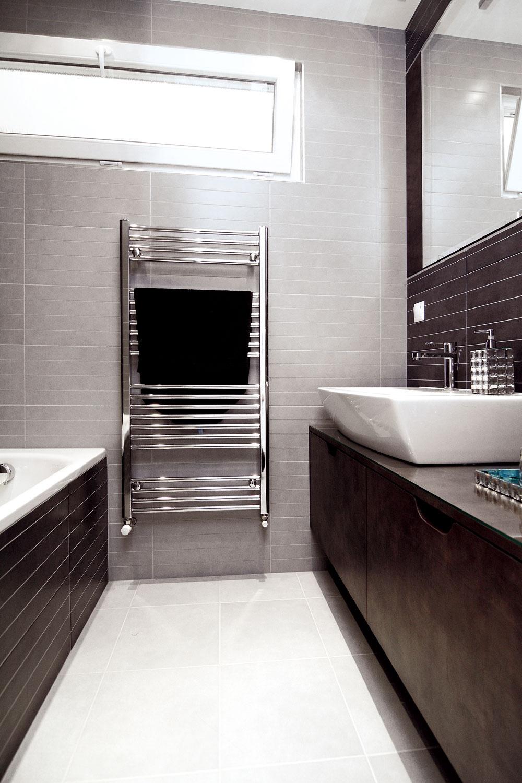 Kúpeľňa zabrala aj priestor bývalej chodbičky, čo jej veľkosti aj možnostiam zariadenia jednoznačne prospelo. Okno síce nevedie do exteriéru, ale do kuchyne, aj tak však vkúpeľni zabezpečilo denné svetlo, čo bolo jednou zpožiadaviek majiteľa.