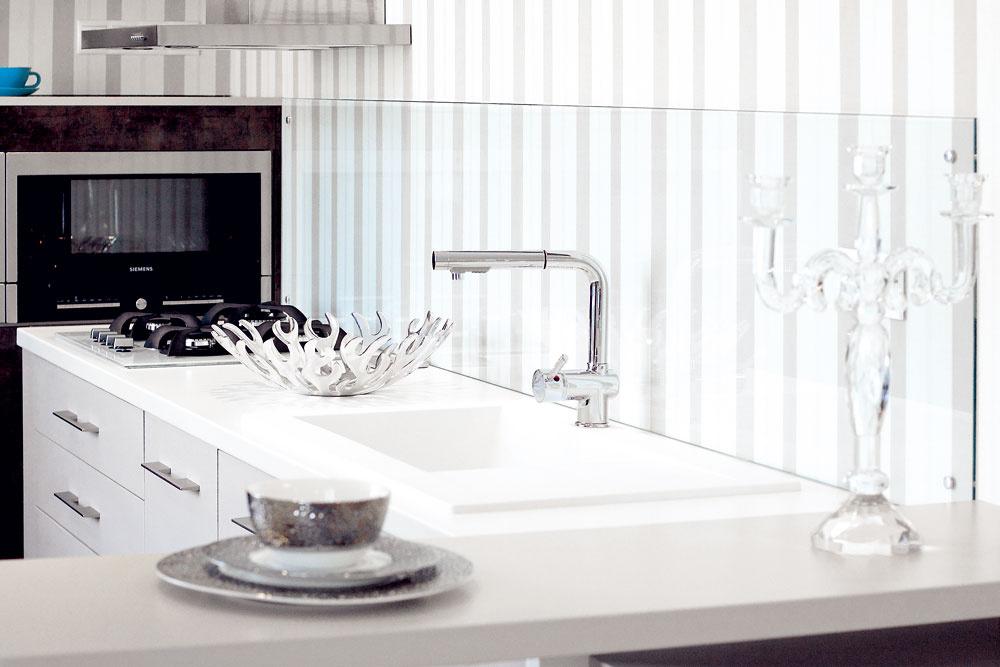 Nanajvýš praktickým prvkom je sklo nad kuchynskou pracovnou doskou. Stena tak môže mať jednotný vzhľad, ale tapeta sa nezašpiní.