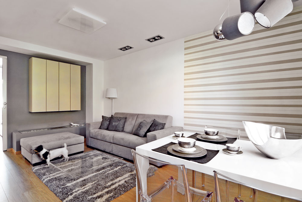Majiteľ bytu chcel jedálenský stôl, za ktorým môžu pohodlne stolovať štyria ľudia. Vďaka priehľadným plastovým stoličkám jedálenská časť denného priestoru nepôsobí preplnene.
