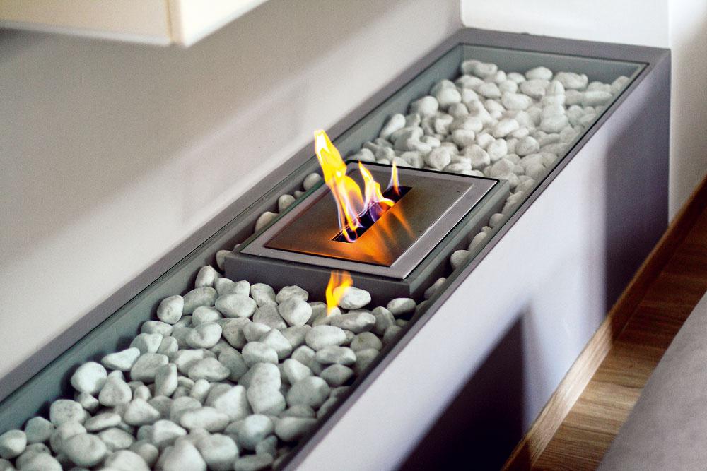 Kozub na bioalkohol nepotrebuje komín, môže tak byť hoci aj vpanelákovej obývačke. Tu je osadený všpeciálnej konštrukcii znehorľavého sadrokartónu, zrovnakého materiálu je aj knižnica nad ním. Aby dvierka skrinky plameň nepoškodil, ich hrany ochránili hliníkovými lištami.