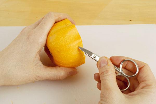 2. Špičkou nožničiek urobte na okraji v pravidelnom rozstupe sedem dierok a jednu dierku spravte v strede tekvice.