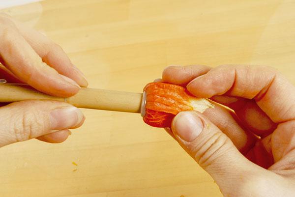 4. Nahrejte aranžérsku pištoľ a na jeden koniec paličky nalepte plod machovky. Do druhého konca vlepte háčik pripravený z drôtika.