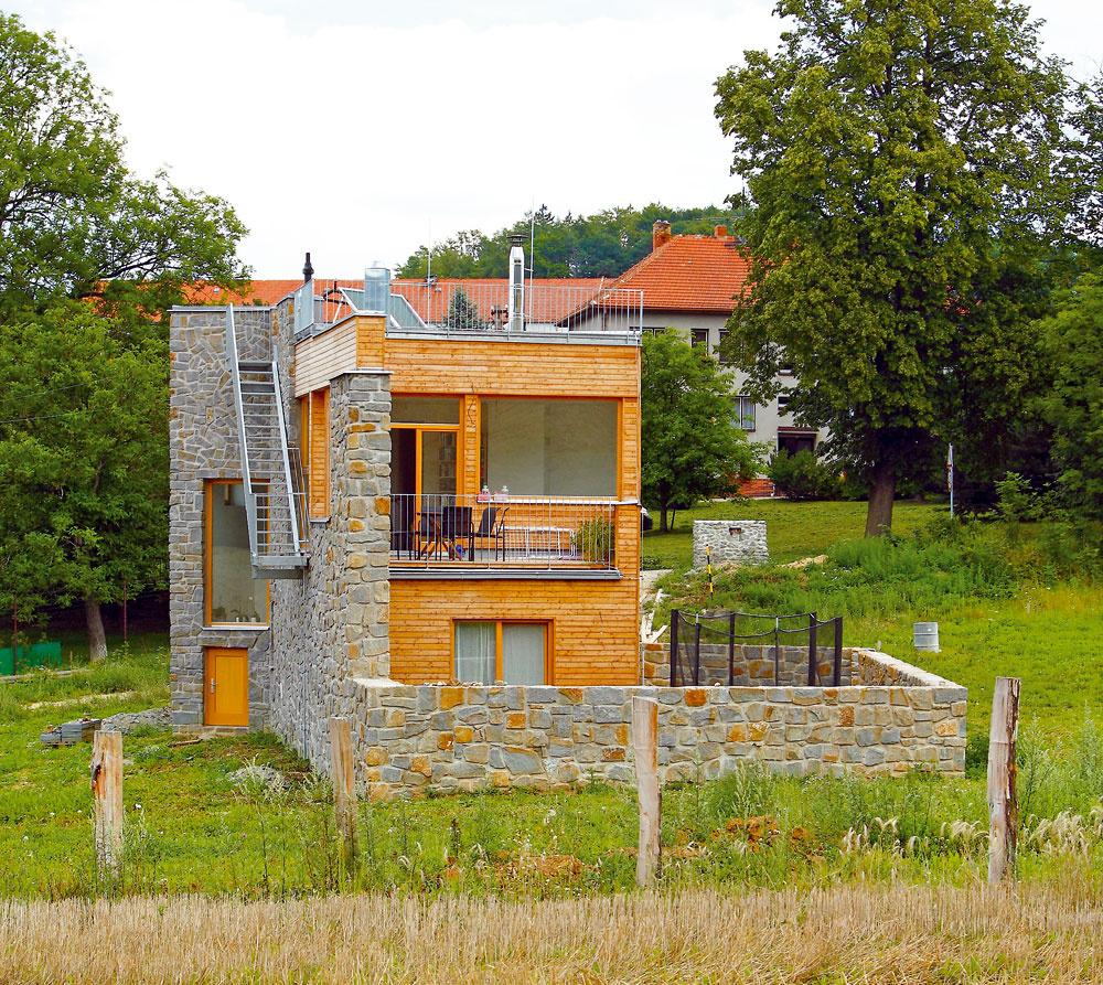 Zjednej strany kamenná pevnosť, zdruhej drevený rodinný dom. Kamenný múr chráni stavbu zo severu, na jej západnej strane potom klesne, obtočí sa okolo ako slimák ana juhu vytvorí pred drevenou fasádou malý dvorček. Na západ – kvýhľadu na les – je orientovaná terasa pred obývačkou na poschodí.