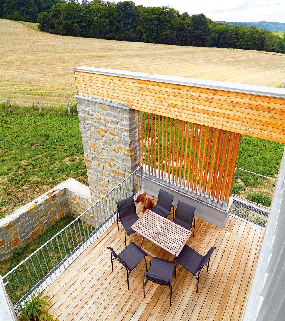 Šikovným otočením dispozície – oproti bežným zvyklostiam hore nohami – dopriali architekti obyvateľom domu všetky atraktívne výhľady: na horizont na juhu, les na západe aj malebné údolie na severe. (Pohľad zo zelenej strechy-terasy na terasu pred obývačkou.)
