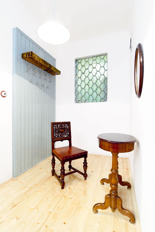 """Vešiakové steny vpredsieni boli pre mestské byty v30-tych rokoch typické. Architekt Krížik chcel tento tradičný prvok oživiť, aby však dosiahol súčasný vzhľad, zvolil na povrchovú úpravu dnes modernú sivú farbu. Vešiakovú stenu urobil zdreveného obkladu, ktorý bol pôvodne vinej miestnosti: """"Snažil som sa oenvironmentálny prístup – znovu využiť staré veci trochu iným spôsobom. Moja filozofia je staré veci nevyhadzovať, ale aktualizovať ich adať im novú šancu."""" Zaujímavým prvkom je aj neobvyklý kubistický sklobetón, ktorý do predsiene vpúšťa denné svetlo zo svetlíka."""