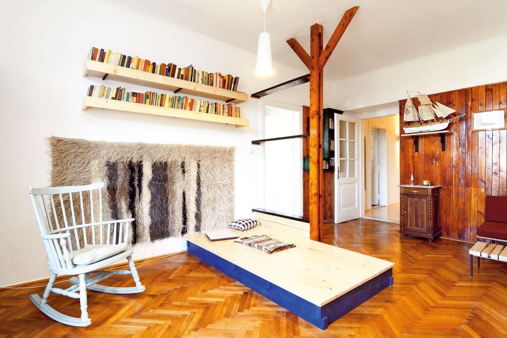 """""""Nie je to klasická obývačka – stena stelevízorom, oproti veľká sedačka… Vtakom priestore môžete akurát tak pozerať televíziu,"""" vysvetľuje architekt. """"Ja mám radšej, keď sú vbyte rozličné 'kúty' srôznou atmosférou akeď je dispozícia variabilná. Aby mohol niekto sedieť tu aniekto naproti, prípadne sa môžu preniesť kreslá… Vyvýšené drevené pódium sa dá využívať ako relaxačný priestor, miesto na sedenie, čajovňa, môže sa tu hrať dieťa… Avprípade potreby poslúži ako posteľ – stačí naň položiť matrac."""
