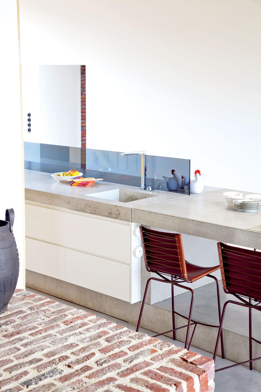 Veľký betónový stôl slúži ako kuchynská linka, jedálenský stôl, písací stôl pre deti ipracovná doska.