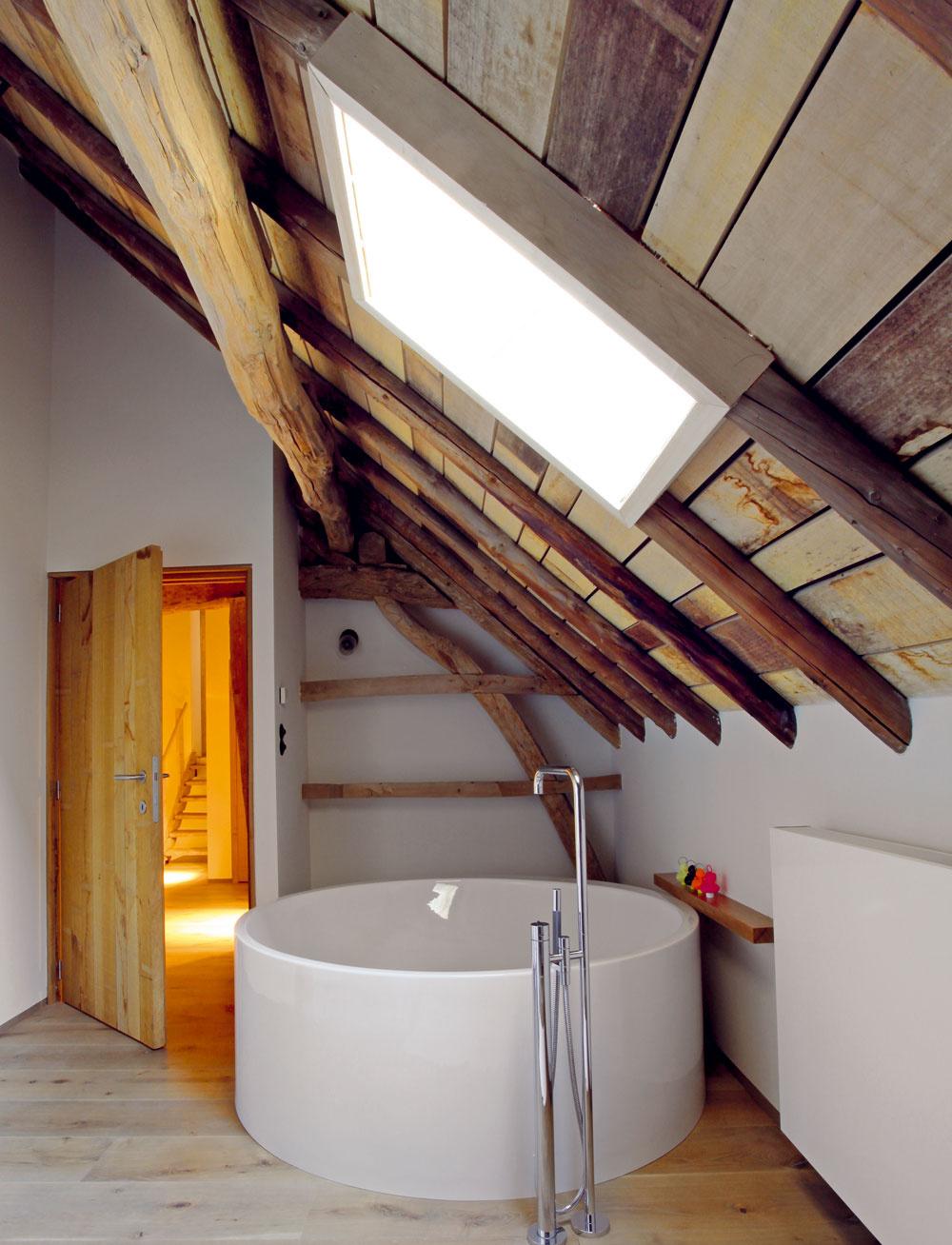 Veľkorysá kúpeľňa je vybavená vaňou, ktorá tvarom pripomína kaďu, atmosféru vidieka potvrdzuje aj odkryté drevo nahrubo opracovaného krovu.