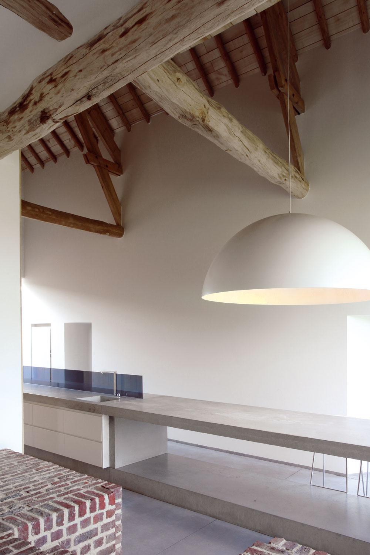 Otvorený krov znahrubo opracovaných kmeňov kontrastuje sminimalisticky poňatým interiérom abetónovým stolom.