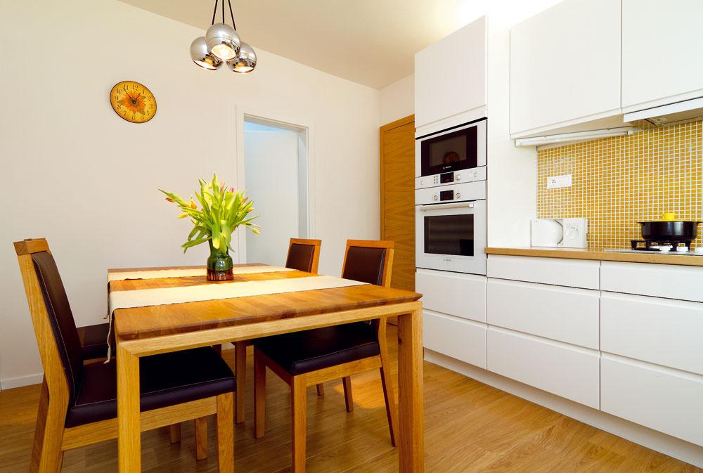 """Nová kuchyňa mala byť jednoduchá amoderná, rovnako aj žlto-oranžový obklad vkombinácii s bielou farbou skriniek boli požiadavkami pani Svetlany ajej dcéry. Linku nakoniec vybrali vkike: """"Bolo to riešenie – dobrá kvalita za rozumnú cenu,"""" hovorí architektka. Dvierka azásuvky so zapustenými úchytkami podporili čistý moderný vzhľad miestnosti. Keďže ku kuchyni prilieha špajza (vedú do nej biele dvere, drevenými sa do kuchyne vchádza), ktorá je tu hlavným úložným priestorom na potraviny amiesto vnej má aj chladnička, nemusela architektka preplniť kuchyňu skrinkami ani vysokými """"komínmi"""". Miestnosť tak pôsobí vzdušne."""