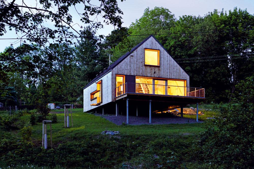 Architekti osadili dom takmer na pozdĺžnu os pozemku, stavba teda akoby levitovala nad lúkou.