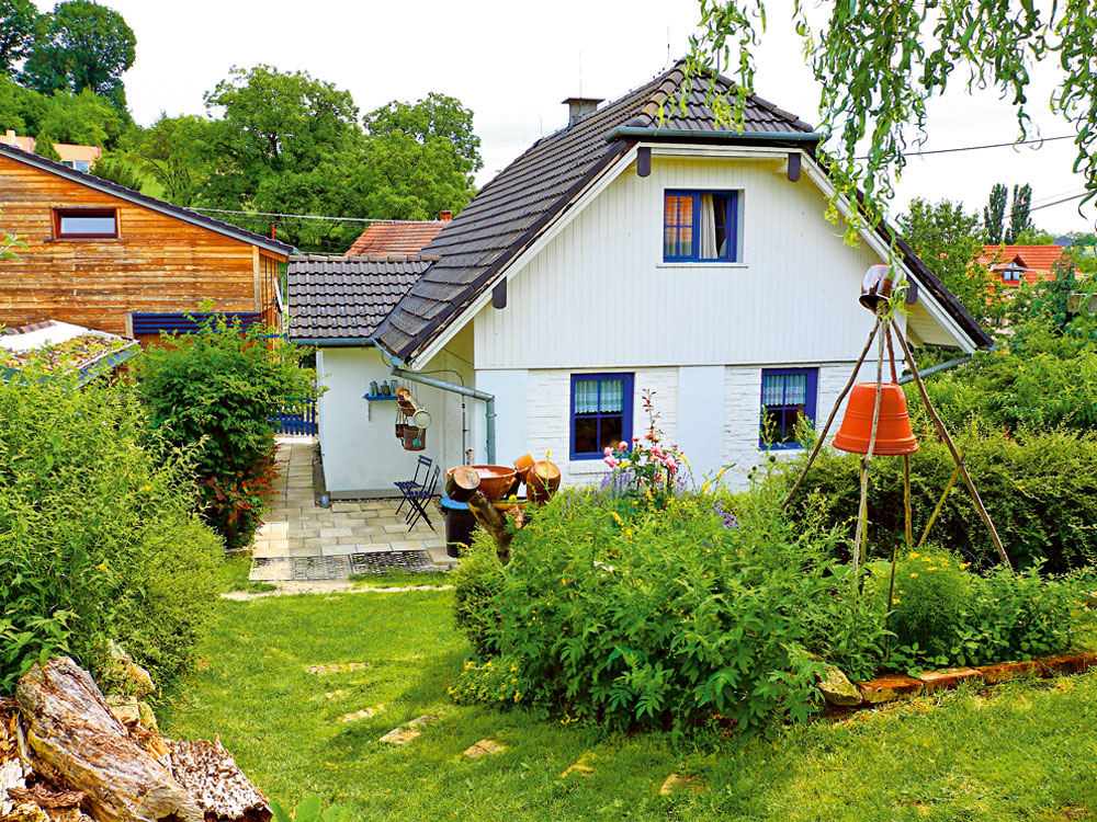 Rodinný dom (vpredu) sa od penziónu (vzadu) líši štýlom aj farbou. Vľavo vrohu je torzo práchnivejúceho stromu. Ten podľa ekológov slúži ako úkryt pre užitočný hmyz.