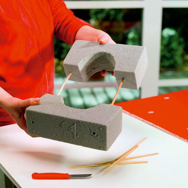 Štvorcovú základňu tvoria dva kvádre zaranžérskej peny. Do každého sme vyrezali polkruh tak, aby sa sem dal neskôr umiestniť kvetináč. Oba kvádre sme potom spojili pomocou drevených kolíkov (môžu sa použiť aj špajle).