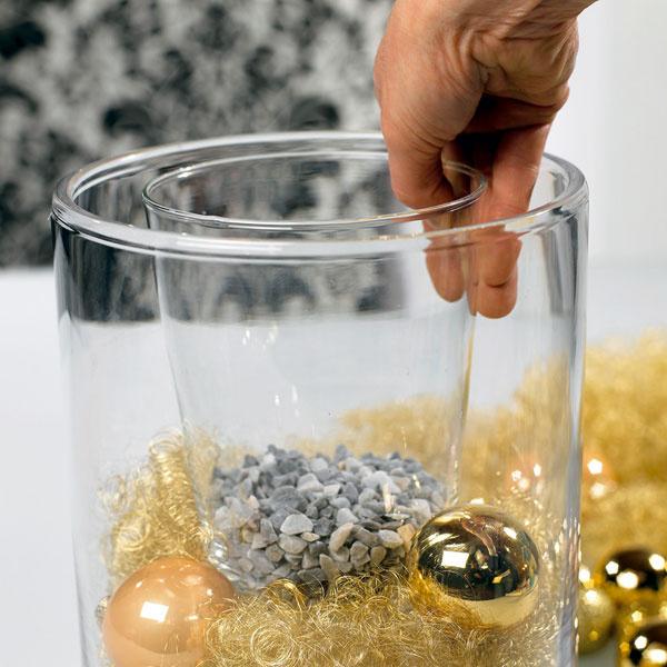 Dovnútra sme umiestnili druhú, menšiu vázu (môžete použiť aj jednoduchý plastový obal na kvetináč), strochou štrku na dne – štrk alebo granulát je dôležitý na zaťaženie, aby nádoba pevne stála na svojom mieste.