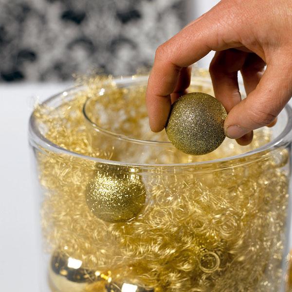 Priestor medzi vázami sme vyplnili zlatými vlasmi afarebne zladenými mäkkými vianočnými guľami. Nakoniec sme už len vložili do vnútornej vázy krémovú poinsettiu vnajväčšej veľkosti.