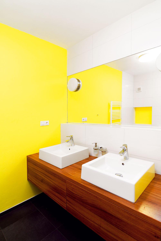 Nová kúpeľňa vznikla na rovnakom pôdoryse ako jej predchodkyňa. Overená kombinácia farieb: čierna podlaha, biele obklady, žlté steny adrevo, pôsobí útulne ačisto zároveň apriestoru bez prirodzeného osvetlenia dodáva teplo aj pozitívnu energiu.