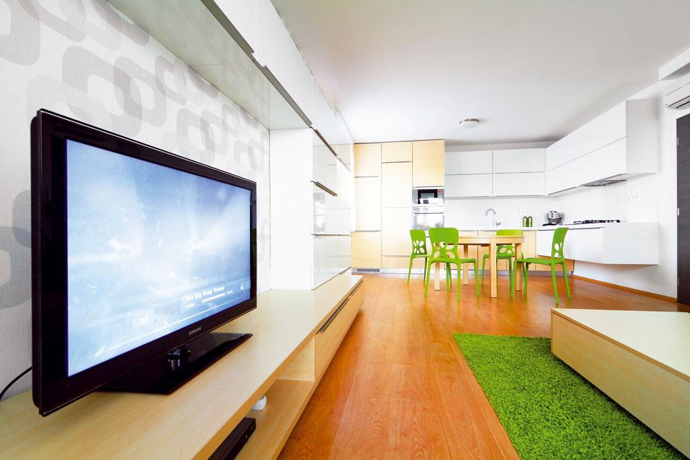 """Vnovej kuchyňo-obývačke sa našlo miesto na priestrannú rohovú linku, rozkladací jedálenský stôl pre 4 až 6 osôb aveľkú rohovú sedačku. Zladenie farieb amateriálov vjednom priestore považoval autor interiéru, architekt Rudolf Lesňák, za samozrejmosť. Na oživenie inak farebne striedmeho zariadenia využil vtomto prípade sviežu zelenú. """"Zelená zároveň kompenzuje červenkastý odtieň podlahy,"""" chváli voľbu domácich architekt. Jasnú farbu však do neutrálneho základu priniesli len jedálenské stoličky akoberec pri sedačke, časom ich môže podporiť ešte pár ďalších doplnkov. Aak obyvateľov bytu zelená omrzí, nebude veľký problém presedlať na inú farbu."""
