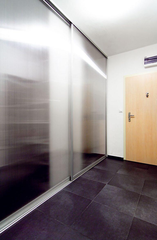 Vpôvodnom byte bola vstupná časť rozdelená priečkou na predizbu ašatník. Výmenou šatníka za dve oddelené niky, skryté za posuvnými dverami, sa získalo množstvo prehľadne usporiadaného adobre prístupného odkladacieho priestoru – ten napravo (bližšie pri dverách) slúži na uskladnenie sezónnych vecí, ten vľavo (pri kúpeľni) ako šatník apráčovňa. Dvere zpriesvitného lexanu pôsobia odľahčene apredsieň opticky nezmenšujú. Tým, že sa všatníku našlo miesto aj na práčku, sa uvoľnil priestor vkúpeľni, ktorá takisto pôsobí vzdušnejšie.