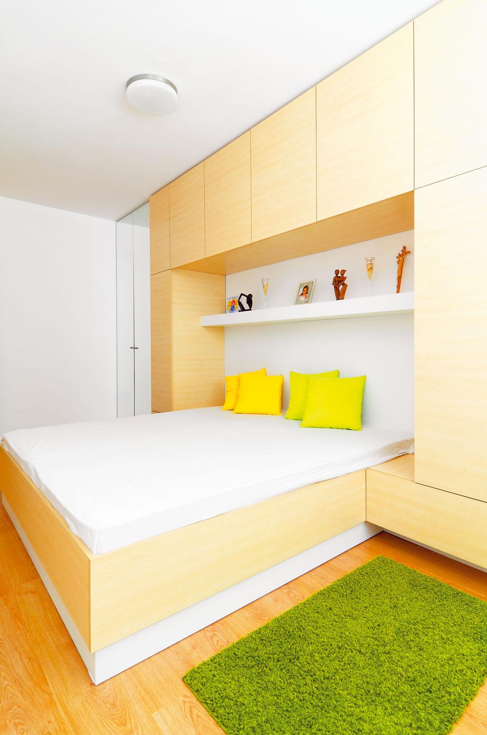 Rodičovská spálňa je pomerne úzka aštandardná šatníková skriňa sa sem nezmestila. Architekt vyriešil tento problém špeciálnym kusom nábytku – posteľou aj skriňou vjednom. Všetky úložné priestory sú navrhnuté vskrini za posteľou, tak, aby miestnosť nepôsobila zapratane.