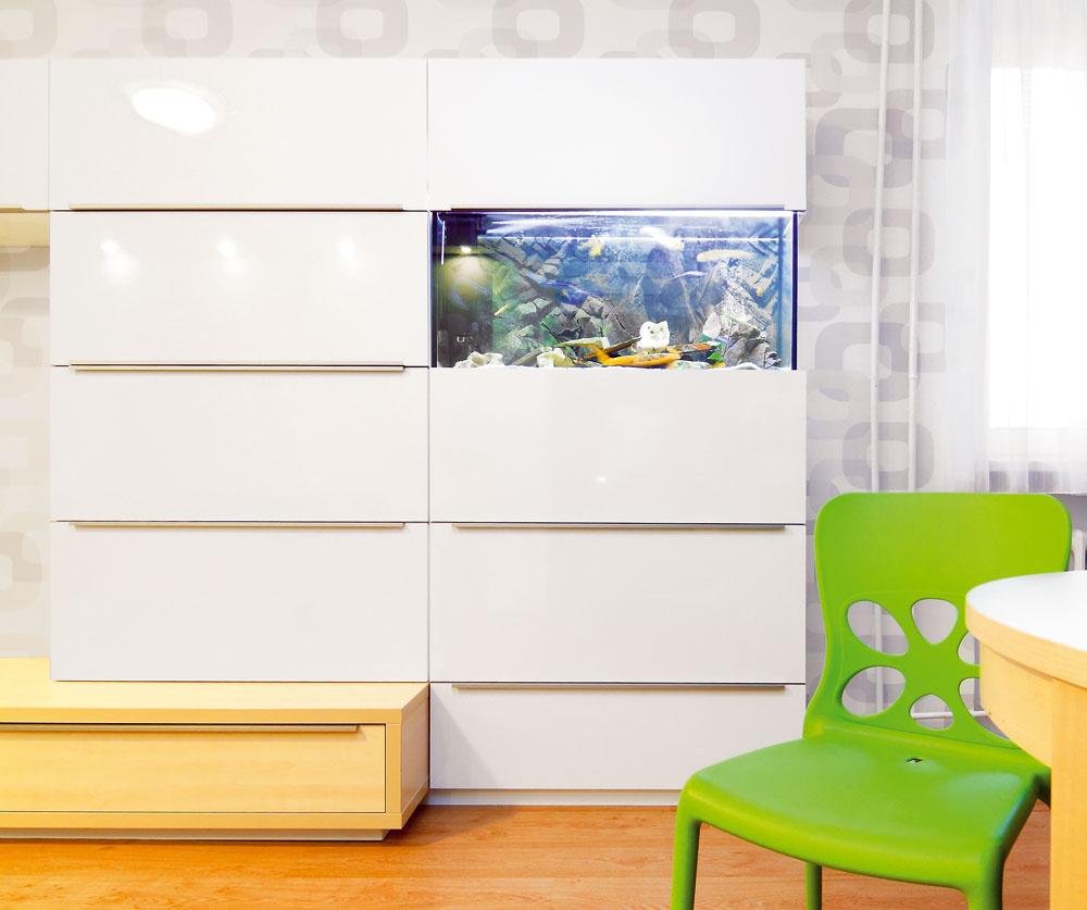 """Tapeta oživuje stenu za televízorom, akvárium zabudované vnábytku vnáša do obývačky skutočný život. """"Akvárium bolo špeciálnou požiadavkou, ktorá ma celkom potešila,"""" priznáva architekt. """"Je to veľmi atraktívny, ale zároveň aj veľmi špecifický interiérový prvok, takže ho ľudia chcú iba výnimočne – investor totiž musí mať ktejto záľube naozaj vzťah."""" Napriek subtílnemu vzhľadu obsahuje zostava skriniek dostatok úložných priestorov."""