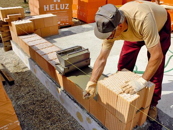 Murovanie z brúsených tehál Heluz s integrovanou polystyrénovou izoláciou sa robí na celoplošné lepidlo, ktoré sa na tehly nanáša pomocou valca.