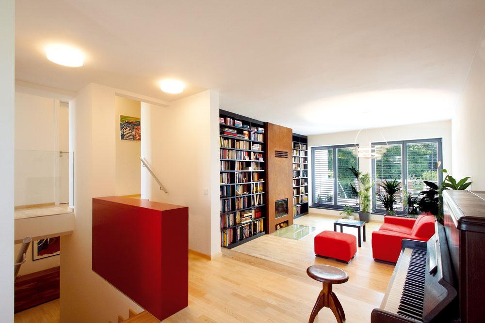 Spôsob, akým architekt vyriešil zábradlie, majiteľku nadchol. Oceňuje ako jeho funkčnú, úložnú podobu, tak aj sklenený priehľad zposlednej úrovne domu. Ústrednou farbou celého obývacieho priestoru je láskavá červená.
