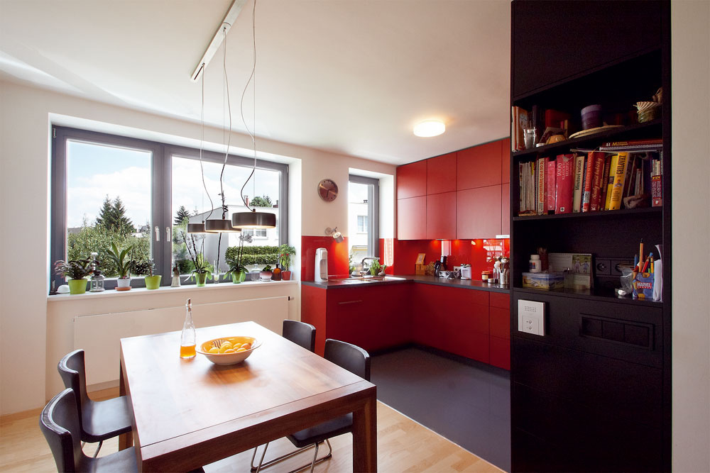 Rozkladací jedálenský stôl zorechového dreva, ktorý vyrobili na zákazku vrovnakej dielni ako väčšinu nábytku, si majitelia priviezli zo svojho predchádzajúceho domova. (Prostredné ztroch detí si na ňom dokonca písavalo úlohy.) Orech si sčervenou kuchyňou vyslovene rozumie.