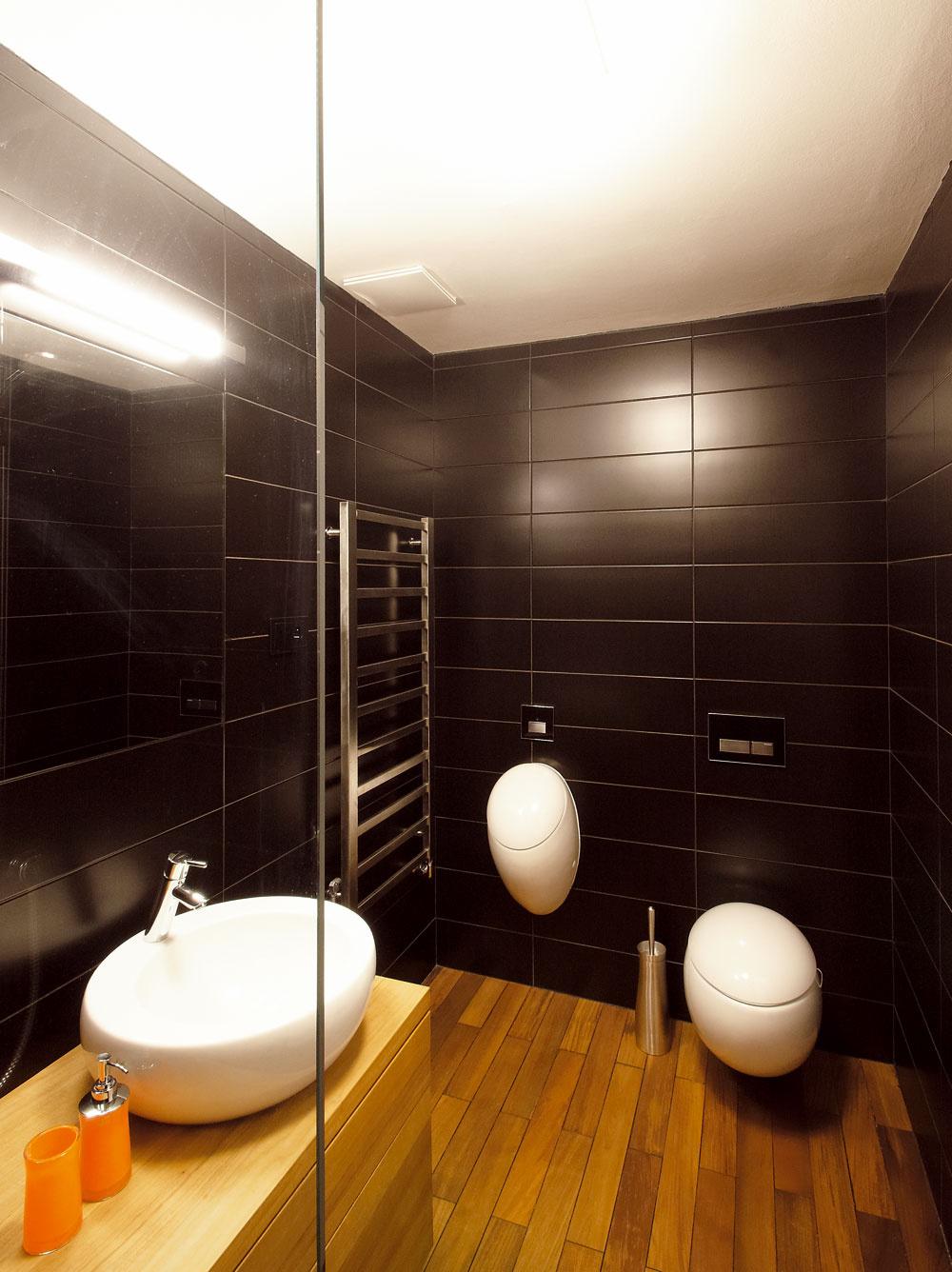 Manželova požiadavka bol splnená – vkúpeľni má pisoár, hneď vedľa klasickej misy. Kúpeľňa je ladená do prírodných tónov aj tvarov – dominantná je tmavá dlažba atíkové drevo. Nájdete ho dokonca aj vsprchovacom kúte.