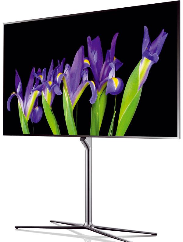 Čo je OLED Nový televízor Samsung ES9500 OLED TV sfunkciou Samsung Multi View ponúka výnimočnú kvalitu obrazu vďaka neobmedzenému kontrastnému pomeru, sýtejšie farby arýchlejšiu odozvu. Obraz je tvorený samostatne svietiacimi pixelmi, zktorých sa dá každý regulovať. Vďaka tomu je táto technológia schopná rozlišovať medzi rôznymi odtieňmi čiernej, takže prináša neobmedzený kontrastný pomer aj vnajtmavších scénach. Realistické farby sú o20 % sýtejšie ako farby na LED televízoroch. Televízor OLED nepotrebuje oddelený svetelný zdroj avyznačuje sa rýchlymi odozvami, čím odstraňuje rozmazaný pohyb aj pri najrýchlejších scénach. Veľmi rýchla odozva tiež umožňuje poskytovať realistické 3D vnemy prakticky úplne bez tzv. duchov. Ultratenký čelný rám, TV sa stenčuje smerom kokrajom kovového rámu, malá zabudovaná kamera sa vysunie, len keď sa používa. Káble aspoje sú skryté vstredovom stojane.