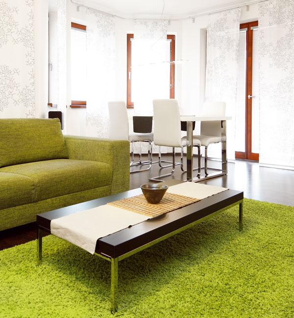 Charakteristickou farbou obývačky je zelená, ktorú sem vniesla sedačka akoberec pod nízkym stolíkom. Smerom ku kuchyni nadväzuje na obývačku jedáleň. Tejto časti denného priestoru dominuje biele stolovanie, ktoré kontrastuje stmavými parketami. Podlaha aďalšie prvky vo farbe wenge celý priestor zjednocujú.