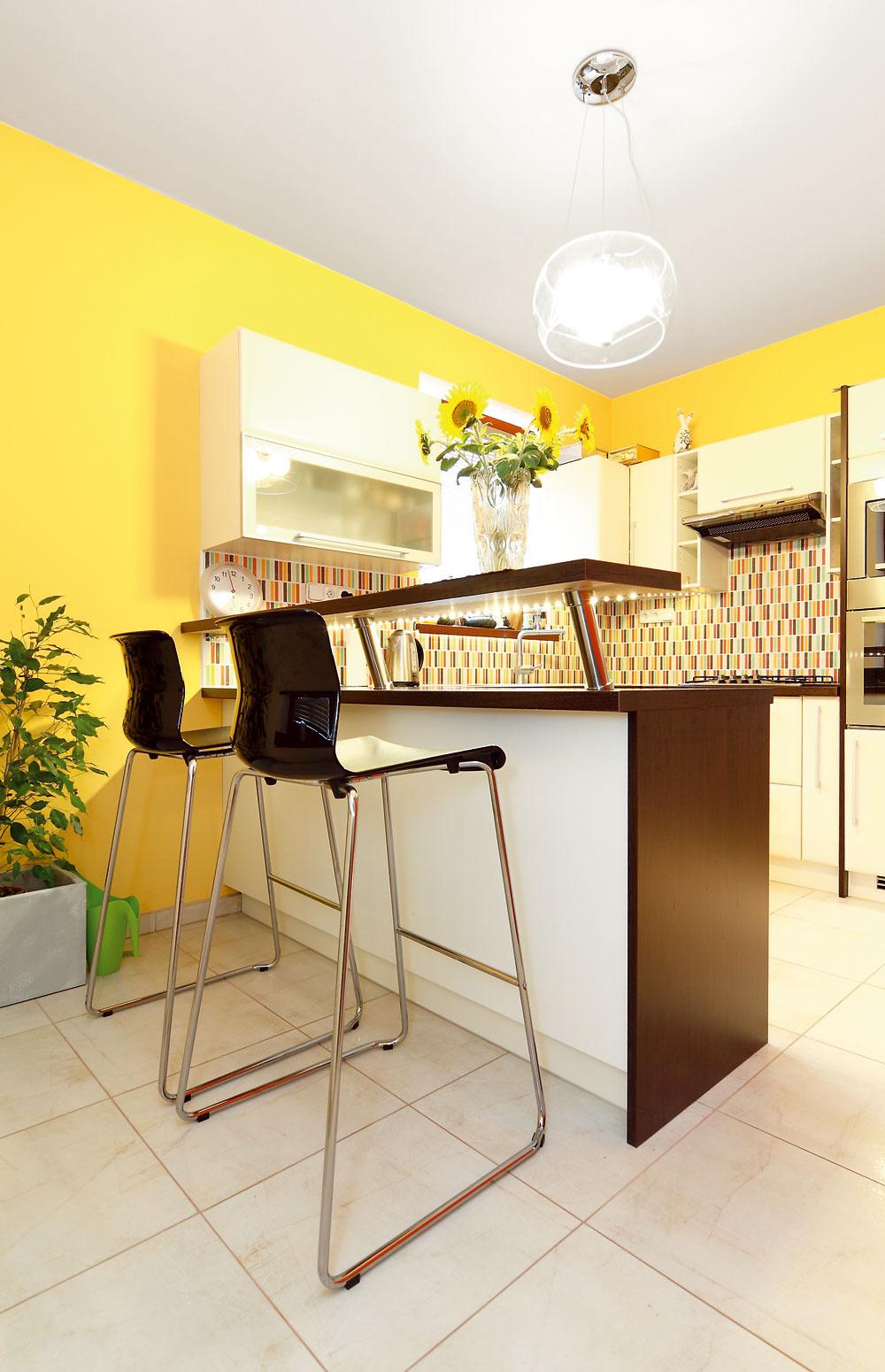 Kuchynská linka zDecodomu už vdome bola, architektka ju však oživila niekoľkými prvkami, ktoré zároveň prispeli kjej zjednoteniu spriestorom obývačky ajedálne. Pribudol barový pult sLED podsvietením sbarovými stoličkami atiež dlhý kvetináč pri stene vedľa barového sedenia, ktorý je dôležitý pre kompozíciu pri pohľade zobývačky. Pôvodnú žltú farbu stien vkuchyni ponechali – ladí so zeleným zariadením obývačky, previazanosť týchto dvoch priestorov podporilo aj rovnaké centrálne svietidlo.