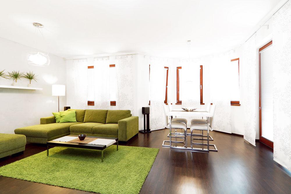 """Vobývačke sa začalo doslova od podlahy – tá nová je vo farbe wenge. Pre laminát sa majiteľ domu rozhodol, pretože vňom bolo podlahové vykurovanie. Stmavou dlážkou kontrastujú biele steny, ktoré interiér odľahčujú, presvetľujú apriestor vďaka nim nepôsobí stiesnene. Zvláštnosťou je """"dvojfarebný"""" nábytok – na každej zo stien totiž použila architektka inú farebnú kombináciu. Kým oproti sedačke vytvárajú výrazný kontrast sbielou omietkou skrinky vo farbe wenge, ktoré korešpondujú sodtieňom podlahy, susedná stena patrí jemnej kombinácii bielych políc abetónovosivého podkladu. Farebnú kompozíciu príjemne dopĺňa zelená, reprezentovaná sedačkou, kobercom aizbovými rastlinami."""