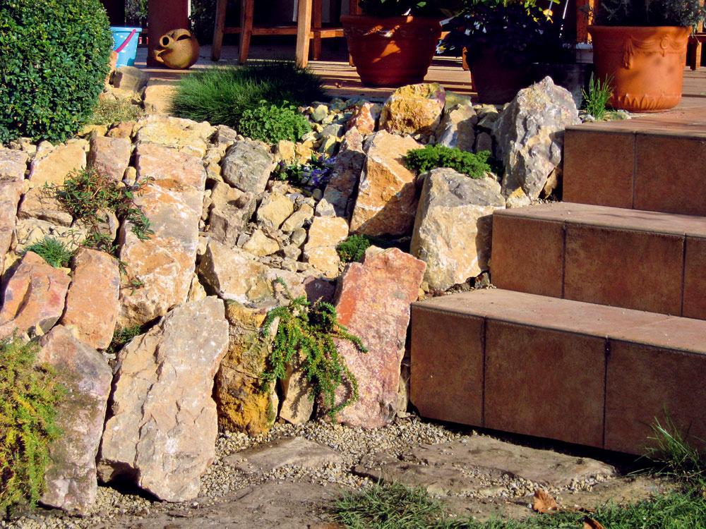 Masívnejšími kameňmi sa zakryl betónový základ terasy aschodov, ktorý pôsobil rušivo pri pohľade zboku. Teraz skalka viac splýva do jedného celku so schodmi asterasou.