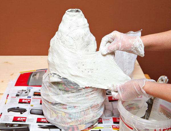 4.Vkýbliku si zmiešajte biely cement svodou. Na jednu vrstvu by mal stačiť 1 kg cementu. Pripravte si ho redší alen po troche, lebo rýchlo tuhne. Do cementu namáčajte kúsky širšieho obväzu aprikladajte ich na vázu.